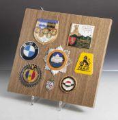 Konvolut von 7 versch. Auto-Plaketten, auf Holzplatte montiert, bestehend aus: a) 1. Internat.