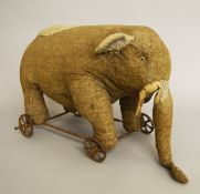 Vintage pull along elephant on cast wheels, height approx. 30 cm.