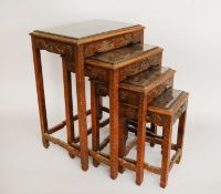 A set of 4 nested tables with oriental style carving. Glazed tops.