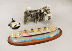A dog ornament together with a model of RMS Titanic 100 years commemorative medallion.