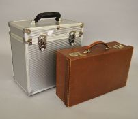 A small vintage travel suitcase together with a modern padded flight-case.