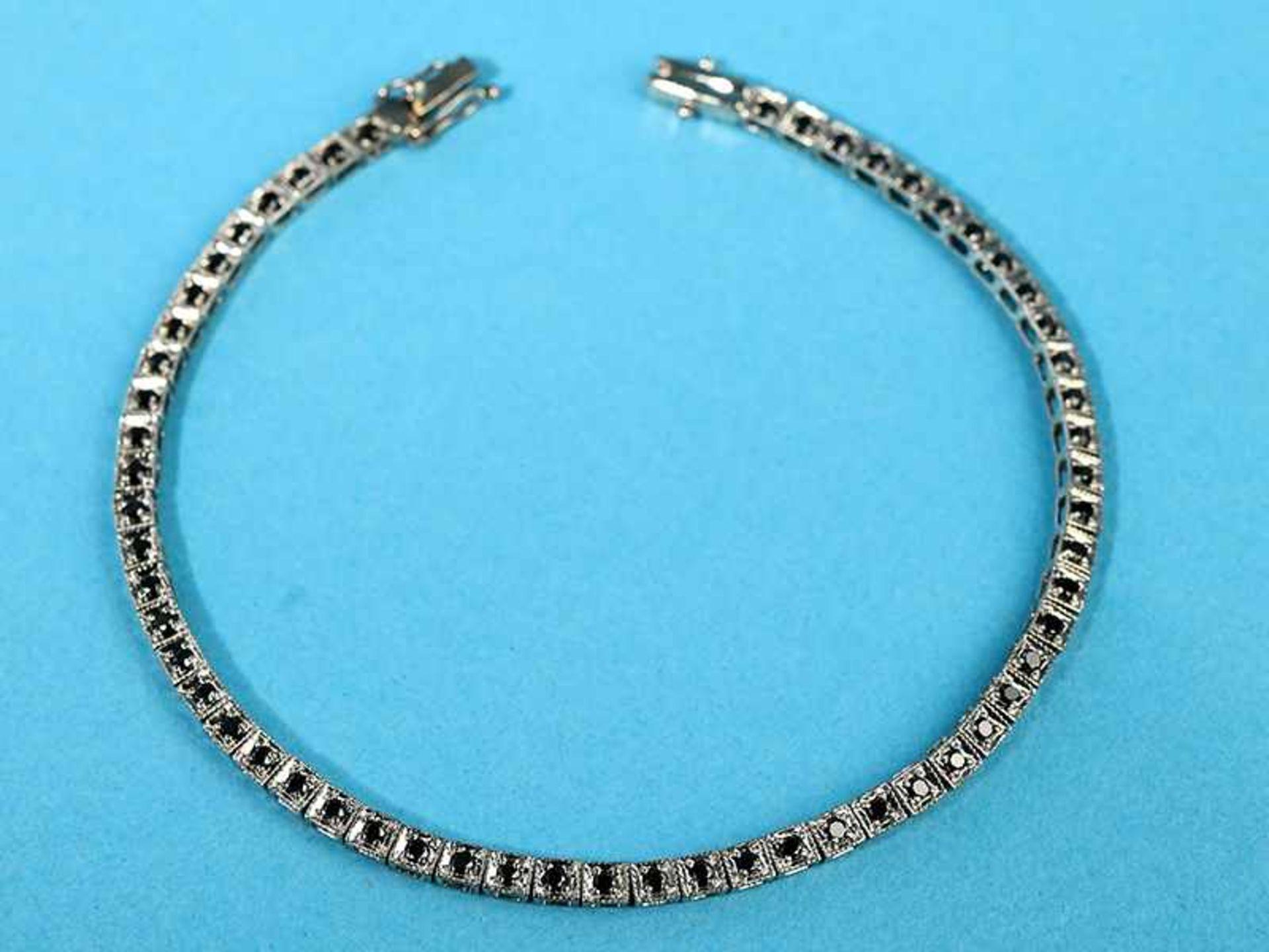 Streifenarmband mit 57 schwarzen Diamanten, zusammen ca. 0,5 ct, 21. Jh. 9 kt Weißgold.