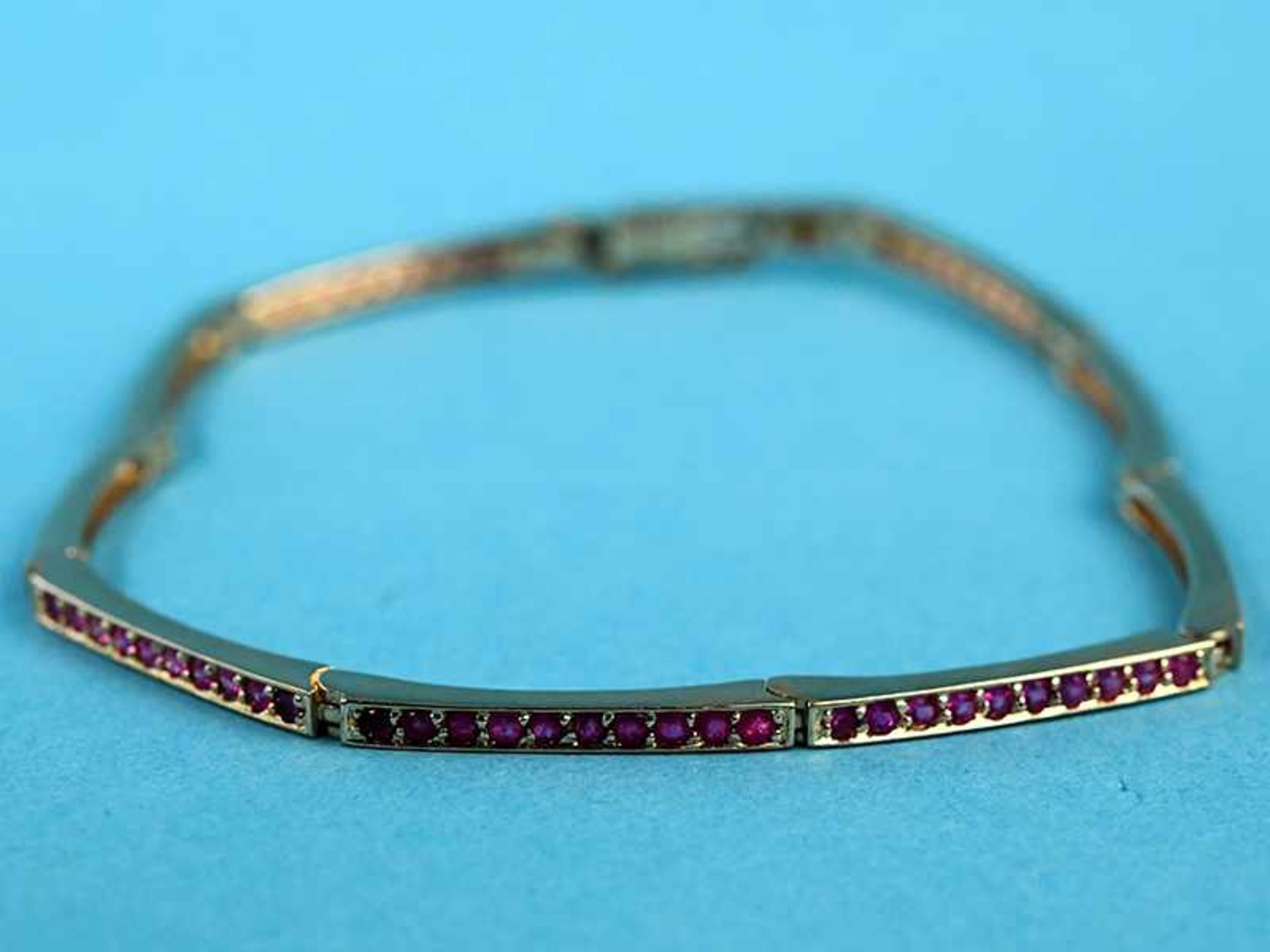 Streifenarmband mit 90 kleinen Rubinen, 21. Jh. 585/- Gelbgold. Gesamtgewicht ca. 9,3 g.
