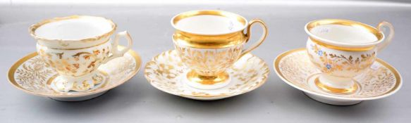 Drei Tassen mit Untertasse, aufwendig mit goldenen Ranken und Ornamenten verziert, eine Tasse mit