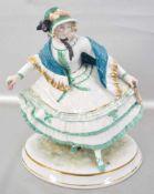 Elegante Dame mit Haube auf ovalem Sockel stehend, mit Fächer und Blüte, bunt bemalt, H 24 cm, B