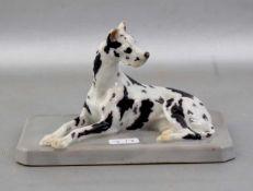 Liegende Dogge auf Sockel liegend, bunt bemalt, am Ohr besch., 12 X 7 cm, FM Heubach