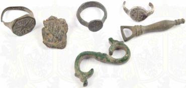 6 BODENFUNDE, Bronze u. Silber(?), 3 Ringe, Phallusanhänger, Verschlusshaken u. Siegel m. bildl.