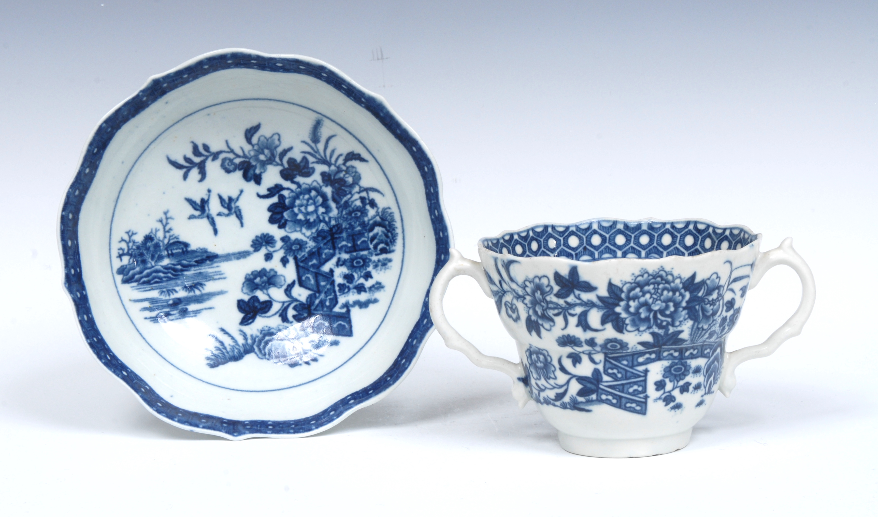 A Worcester Fence pattern ogee shaped chocolate cup and saucer, serpent handles,