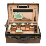A George V green leather travelling vanity case: containing silver and green enamel mounted jars,