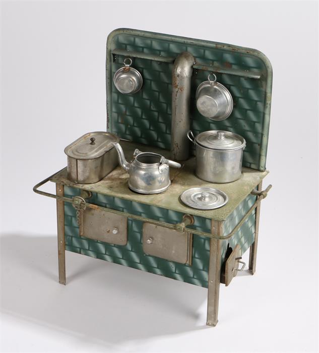 Lot 9 - Tin plate toy oven with green brick effect splash back , central chimney, the hob with fish