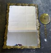 A guilt carved oblong wall mirror and a brass curd skimmer.