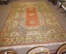 A large terracotta 9 foot by 12 foot patterned rug