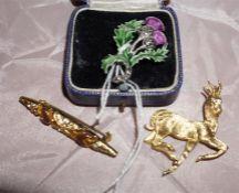 White metal enamalled thistle brooch, yellow metal bar brooch and a yellow metal deer brooch