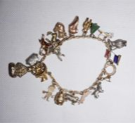 A gold link charm bracelet with 20 assorted charms