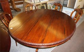 A large rosewood Victorian style round dining table standing on a four caved column base