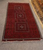 A red, black and ivory Persian rug 78 inches by 40 inches