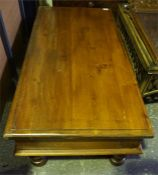 A large mahogany stained teak wood coffee table, oblong shaped with turned legs