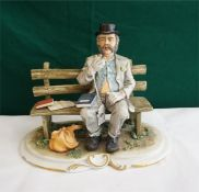 A large Capo-Di-Monte figure of a tramp sitting on a bench