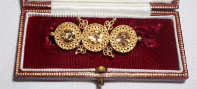 An unmarked gold pierced decorated brooch with rop