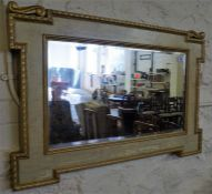 A gilt and painted framed oblong wall mirror, with carved decoration