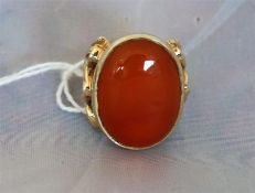 A Ladies gold dress ring set with a large Cornelian, the ring having pierced decorative sides.