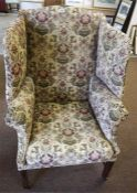 A Georgian style wing Armchair, on square legs and brass roll casters