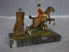 A cold cast hunting table lighter, raised on marble base, in the form of a hunting group