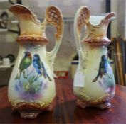 A pair of late 19th century glazed pottery jugs, with bird decoration