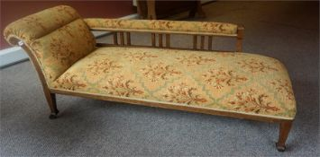 An Edwardian Oak Chaise Longue, upholstered in later gold coloured fabric with floral panels, raised