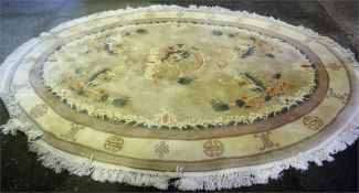 A Chinese Machine Made Rug, of oval form decorated with panels of dragons on a cream ground, 297 x