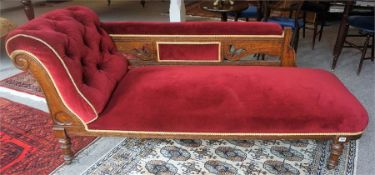 A Late Victorian Oak Framed Chaise Longue, upholstered in later red dralon, raised on turned legs,