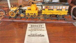 "A Hornby ""Rocket"" Model Of A Locomotive Steam Engine, 30cm high, 85cm wide, raised on wooden plinth,"