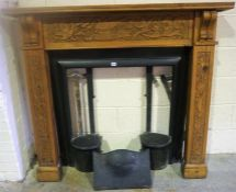 A Carved Wood Fireplace, with painted cast iron insert, to include grate and canopy, (insert 82 x
