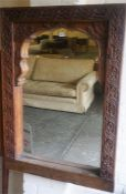 A Large Carved Wood Wall Mirror, the frame is decorated with carved flowerhead roundels, 117cm high,