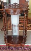 A Victorian Mahogany Canterbury, with urn surmounts and shaped top above fretwork columns and