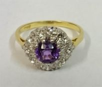 A Ladies 18ct Gold Dress Ring, set with a centre Amethyst surrounded by small Diamonds, ring size O