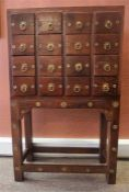 An Indonesian Hardwood Apothecary Style Chest Of Drawers, with four rows of four drawers,