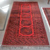 A Kashmir Machine Made Rug, Decorated with five geometric panels on a red ground, 208 x 108cm