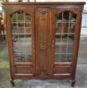 A French Oak Bookcase, with two leaded glazed doors enclosing wooden shelves, 142cm high, 115cm