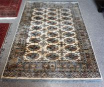 A Kashmir Machine Made Rug, Decorated with nine rows of three geometric panels, on a cream and beige