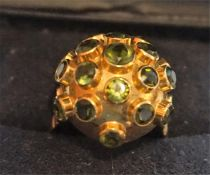 An 18ct Gold & Gemstone Dress Ring, with multiple small green gemstones, raised on a spherical