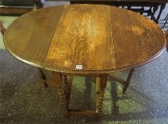 An Oak Gateleg Table, raised on barley twist legs, 70cm high, 108cm long, 77cm wide