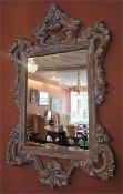 A Modern French Style Wall Mirror, with moulded floral and scroll decoration, 139cm high, 82cm wide