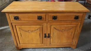 A Vintage Light Oak Sideboard, with two small drawers above two panelled doors, having Arts & Crafts