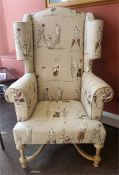A Modern William & Mary Style Wing Armchair, Upholstered in a cream coloured golfing theme, 134cm