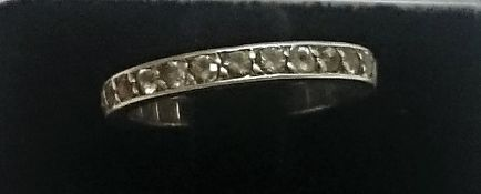 An Eternity Ring, with multiple small stones on a white metal shank,