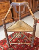 An Arts & Crafts Oak Corner Chair, With a woven rush seat, having a turned column frame with