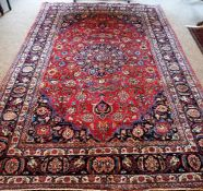 A Large Meshed Rug, Decorated with all over floral medallions and motifs on a red ground, 282 x