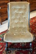 A Victorian Ebonised Nursing Chair, In the form of a gossip chair, with later velour button back