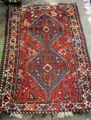 A Small Persian Rug, Decorated with geometric medallions and motifs on a red ground, 127 x 85cm